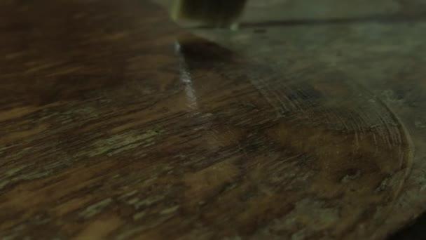 Štětinatý kartáč zblízka. Ruce v ochranných rukavicích. Lakování funguje. Jeden muž lakuje starý dřevěný stůl..
