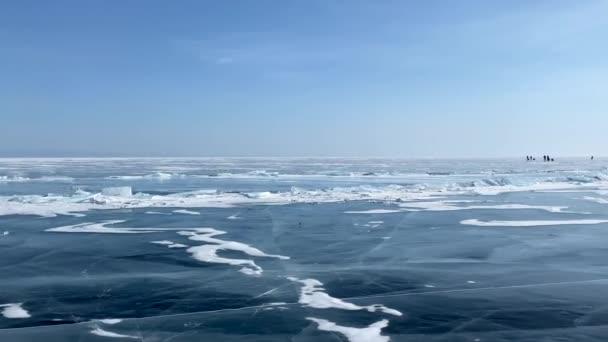 Panoráma fagyott Bajkál-tó egy csoport turista a távolban, utazás korcsolyával. Gyönyörű téli táj, kék átlátszó jéggel, mély repedésekkel, kis hummockokkal és hószigetekkel.