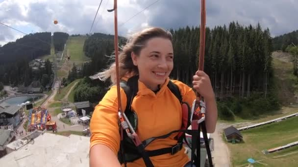 Turistická dívka je na koni nebo posuvné zipline nebo vozík přes přírodu z hor