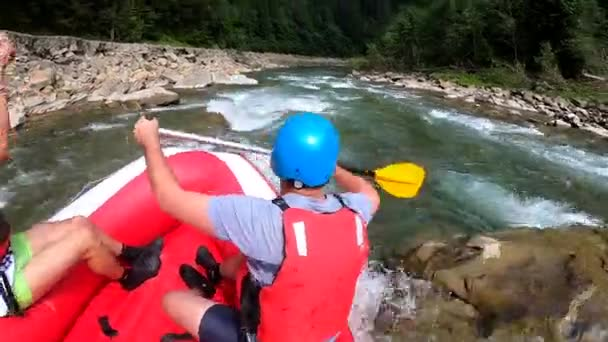 Rafting. Men sit in red inflatable boat, paddle and float mountain river