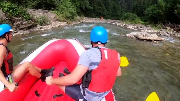 Rafting. Muži sedí v červené nafukovací lodi, pádlo a plovoucí horské řece