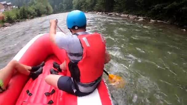 People sit in an inflatable rubber boat and float down the mountain river