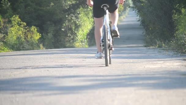 muž na kole, na koni po asfaltové silnici