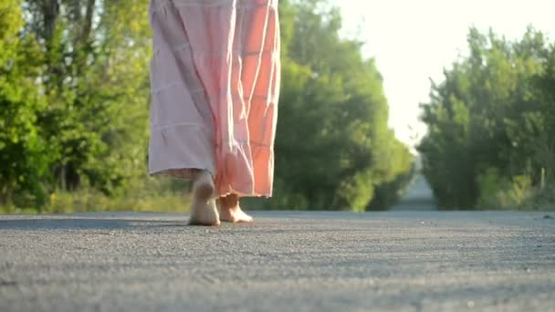girl in a pink dress walking on the road