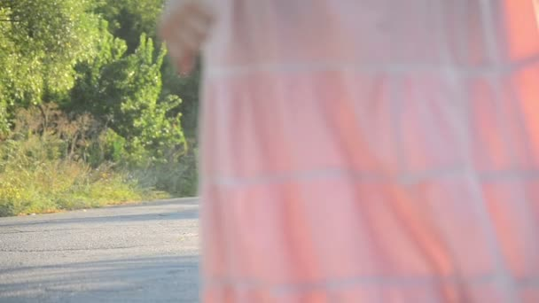 girl in a pink dress goes on the road