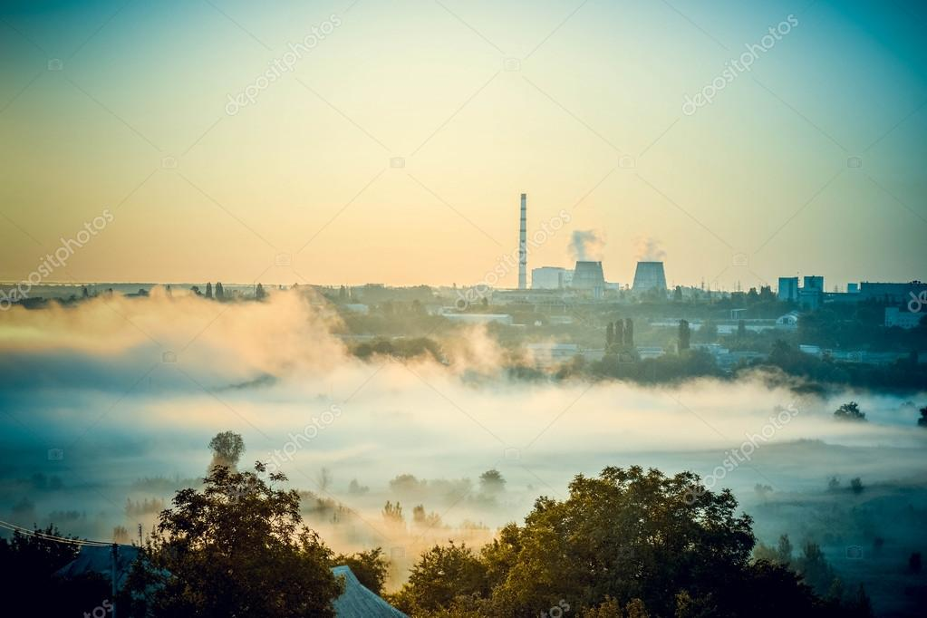 cityscape of power plants and the field with fog