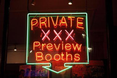 Neon sign of an adult licensed sex shop in a red light district of London at night advertising private preview booths