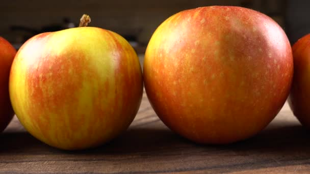 Ripe apples on a wooden board on the background of the kitchen.