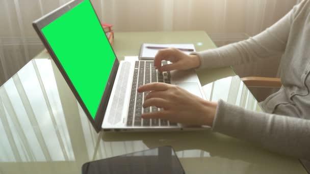 Das Mädchen, das zu Hause im Büro arbeitet, bedient die Tastatur. Der Bildschirm ist ein grüner Hintergrund.