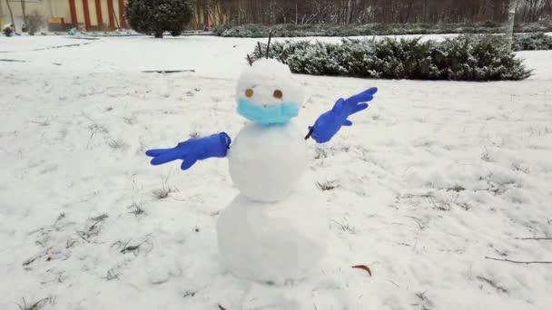 Sněhulák v lékařské masce a rukavicích.