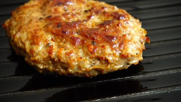 Das gebratene Schnitzel für Hamburger rotiert auf der Grillpfanne.