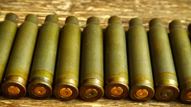 Patronenhülse aus dem Maschinengewehr auf dem Hintergrund eines Holzbretts.