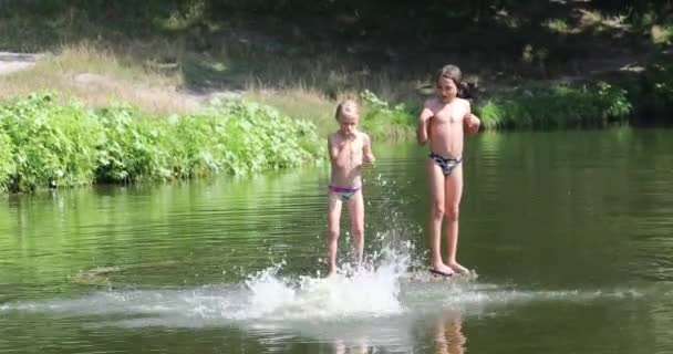 three kids jump in different styles into the water from a bridge on a river on a warm day