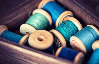 Collection of aqua spools threads arranged in a grunge wooden box