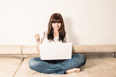 Laughing Woman Sitting on the Sofa with Laptop