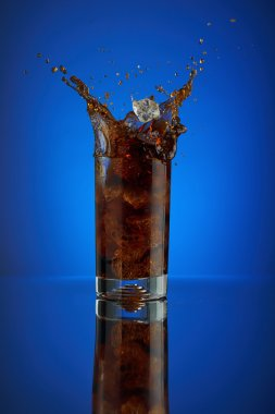 Refreshing splash glass cola soft drink on a blue background. Cool liquid drink coca into a cold glass with ice. Beverage for promoting restaurant and bar. Closeup isolated design brown liquor sparkling.