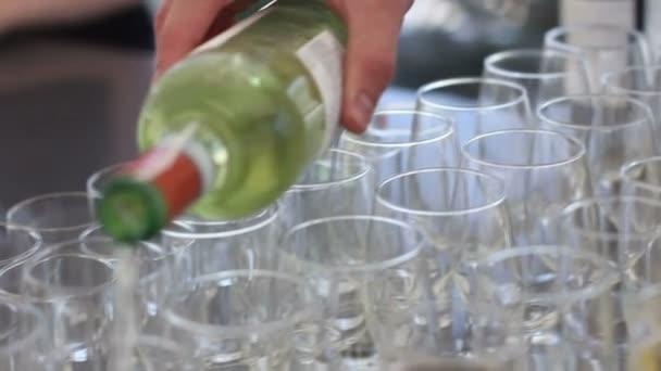 Ruka číšník nalil bílé víno ve sklenici