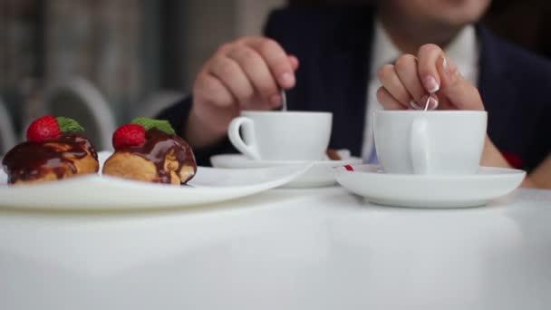 Pár podněcuje cukru v šálku kávy