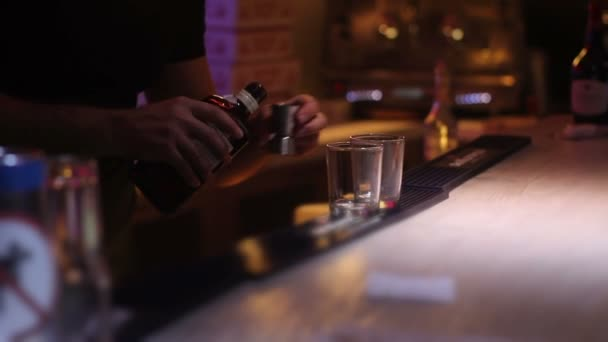 bartender puring a whiskey at nightclub on bar