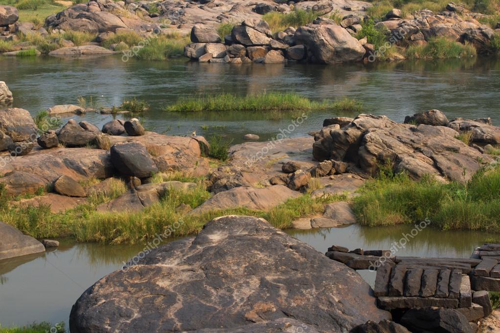 Hampi village Tungabhadra river meadow. Landscape with water, palm, rock, stones. India, Karnataka