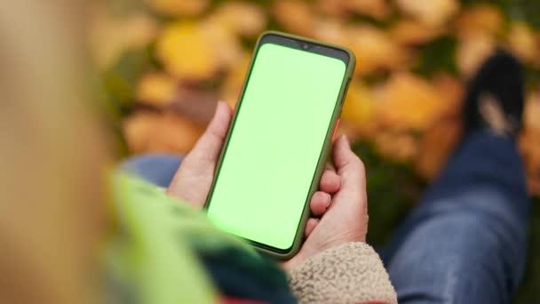 Detailní záběr ženy držící zelenou obrazovku mobilní telefon venku. Blond žena sedí na trávě v parku vedle spadlého listí