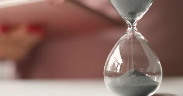 Női kezek kezében egy tabletta fehér asztal háttér. Szürke mágneses por folyik keresztül egy homokóra fehér asztal háttér.