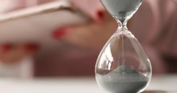 Homok fut keresztül a homokórán. Női kezek kezében egy tabletta fehér asztal háttér.