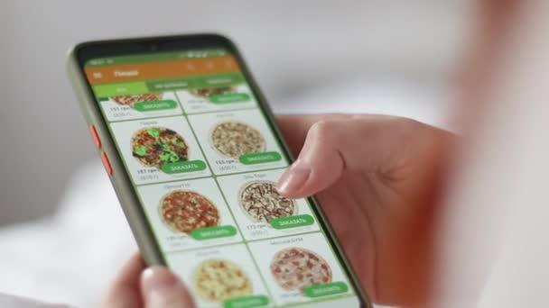 Lebensmittel online per Smartphone-App bestellen Bestellt Pizza im Online-Shop, liegt auf der Couch im Wohnzimmer.. Essenslieferung.