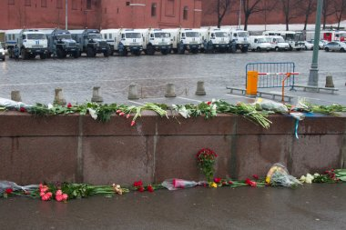 The flowers near a place of murder of the politician Boris Nemtsov and the car of police protecting the Kremlin from march of opposition