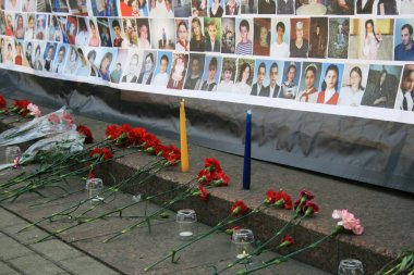 Funeral flowers near a poster with pictures of those killed in the Beslan children. Memorial meeting in Moscow on the anniversary of the terrorist attack