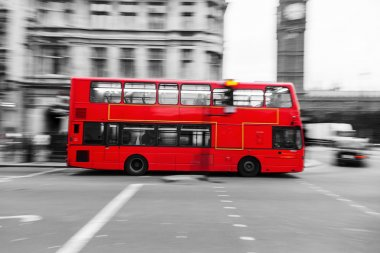Red London Bus in motion blur surrounded by the black and white city of London