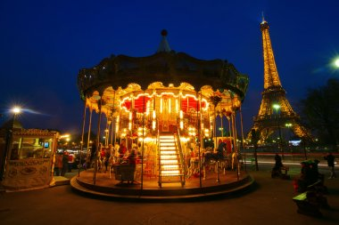 Antique merry go round with the Eiffel Tower in the background at night in Paris, France
