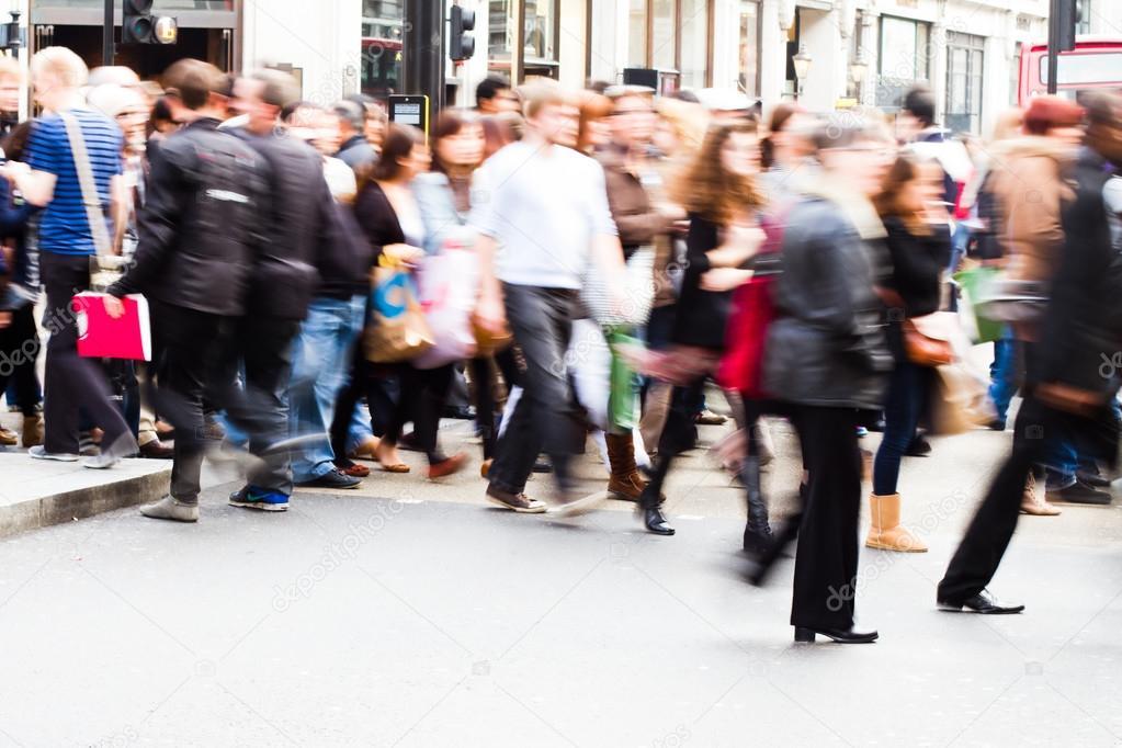 People in motion blur crossing a street in London City