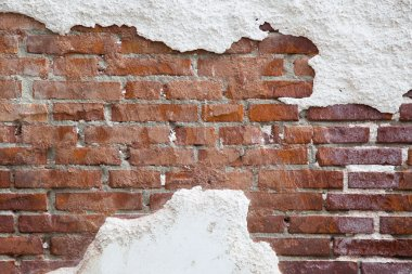 Brick wall with cracked plaster
