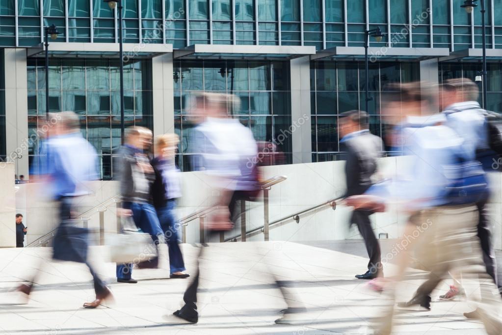 Walking business people in motion blur