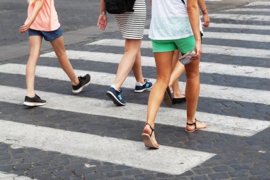 Summery clothed people crossing the street at the pedestrian crossing