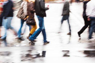 People crossing a wet street in motion blur