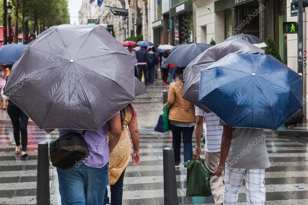People with rain umbrellas crossing a city street on a rainy day