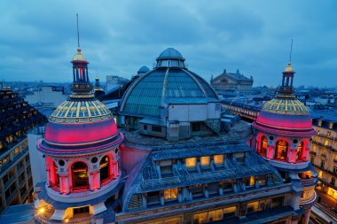 rooftop view of Paris at night with illuminated historical buildings