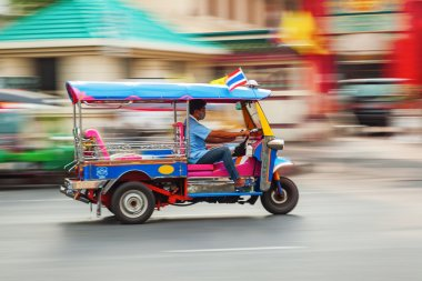 Traditional tuk tuk in Bangkok, Thailand, in motion blur