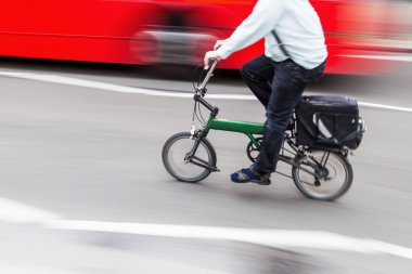 Business man with a folding bike in the city traffic in motion blur