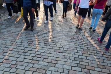 People crowd in backlit walking on cobblestone road