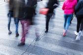 Menschen in Bewegung verwischen auf dem Fußgängerüberweg
