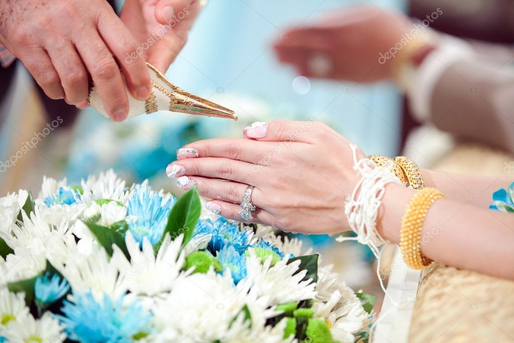 hand of a bride receiving holy water from elders in thai culture