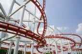 Photo Red roller coasters in amusement park or theme park look fun and  attract large numbers of people to ride and enjoy  its fast and steep drops from high altitudes and inversions which turn upside down