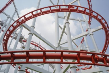 Red roller coasters in amusement park or theme park look fun and attract large numbers of people to ride and enjoy its fast and steep drops from high altitudes and inversions which turn upside down