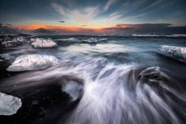 Slow shutter photo showing wave movements around Ice blocks that get washed ashore at black sand beach in Iceland during sunset. stock vector