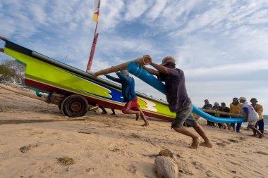 Fishermen push the boat back to shore