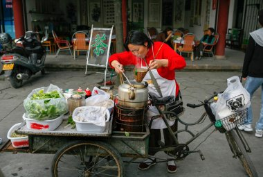 OCt 22, 2006 - Sichuan, China: Street food peddlar prepares noodles at a road side stall in the morning in Sichuan, China. stock vector