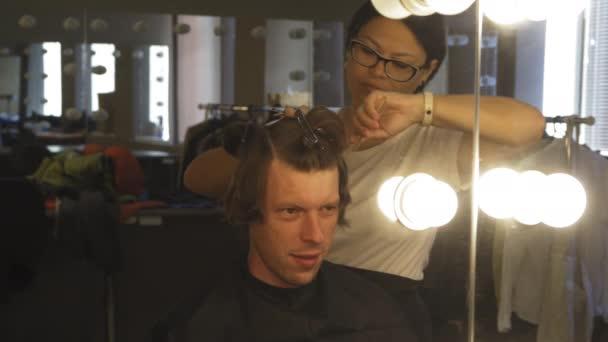 Die Hände der Friseure halten Stücke. Meister macht Haarschnitt mit der Schere. Klient sitzt im Stuhl und schaut Spiegel an.